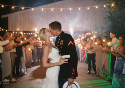 Kissing in front wedding departure line at night with sparklers