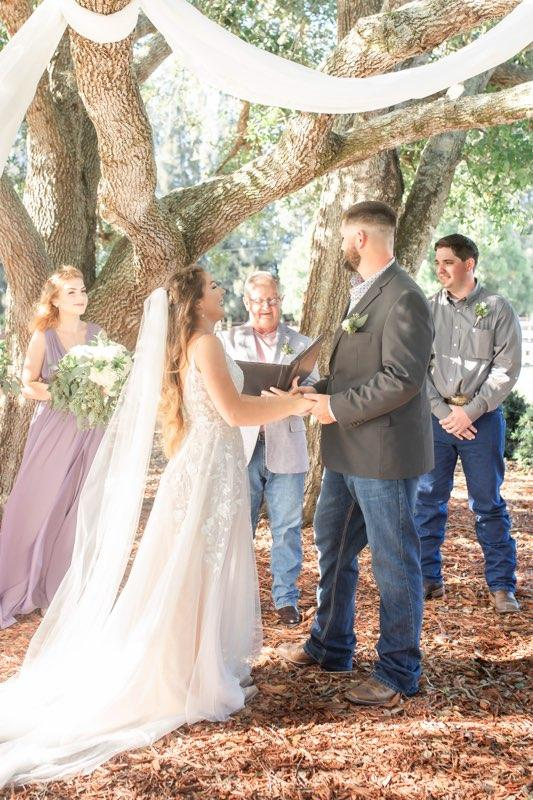 Bride and groom on the ranch making their vows below graceful oak trees