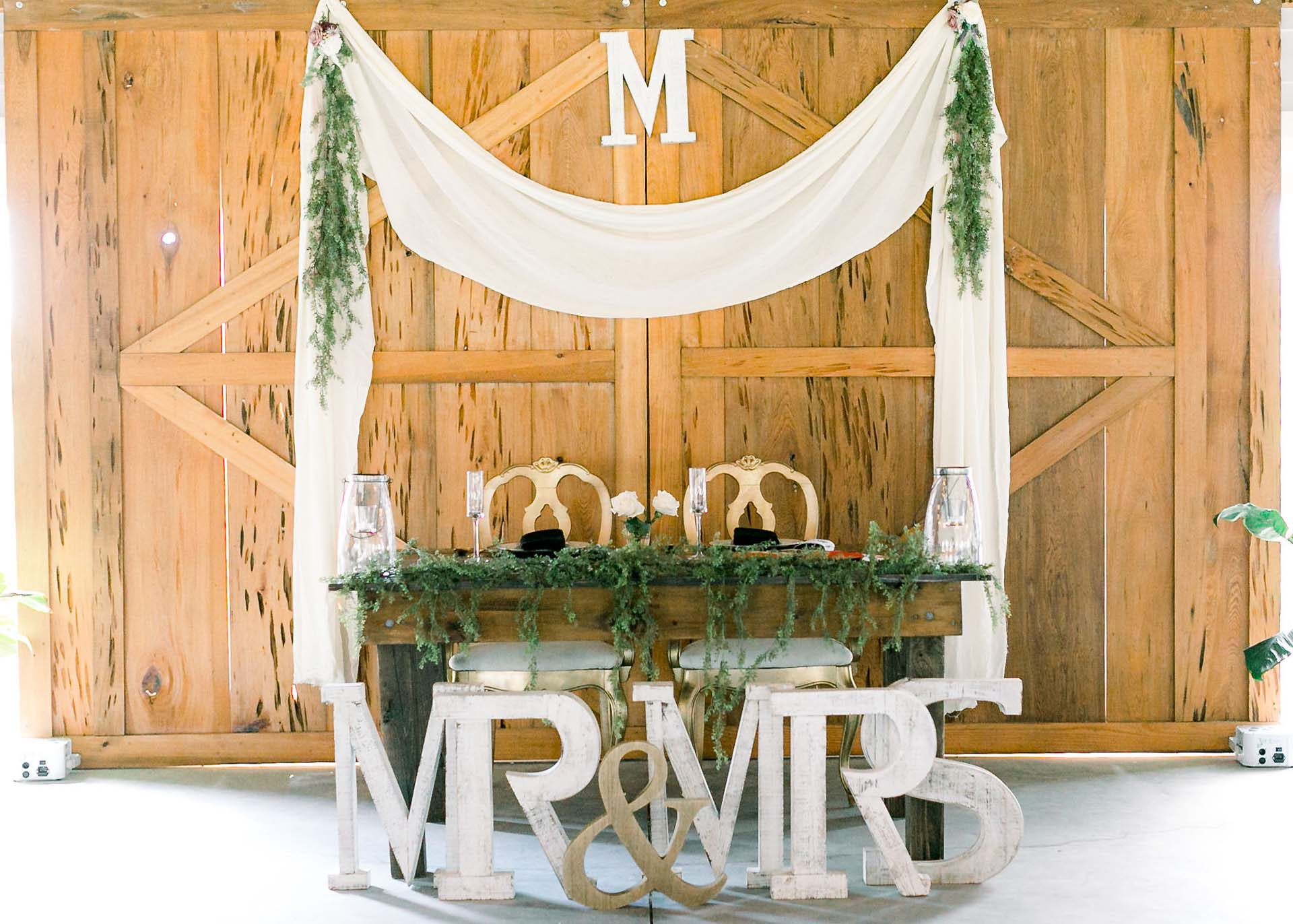Masters Stables wedding venue air conditioned barn-6 bride and groom table. Rustic Barn doors.