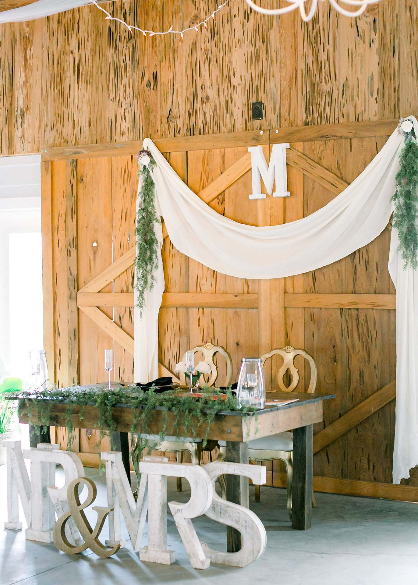 Masters Stables wedding venue air conditioned barn-7 bride and groom table. Rustic Barn doors.